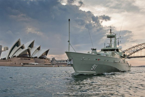 An ARMIDALE Ocean Patrol Vessel passes Sydney Opera House and Harbour Bridge